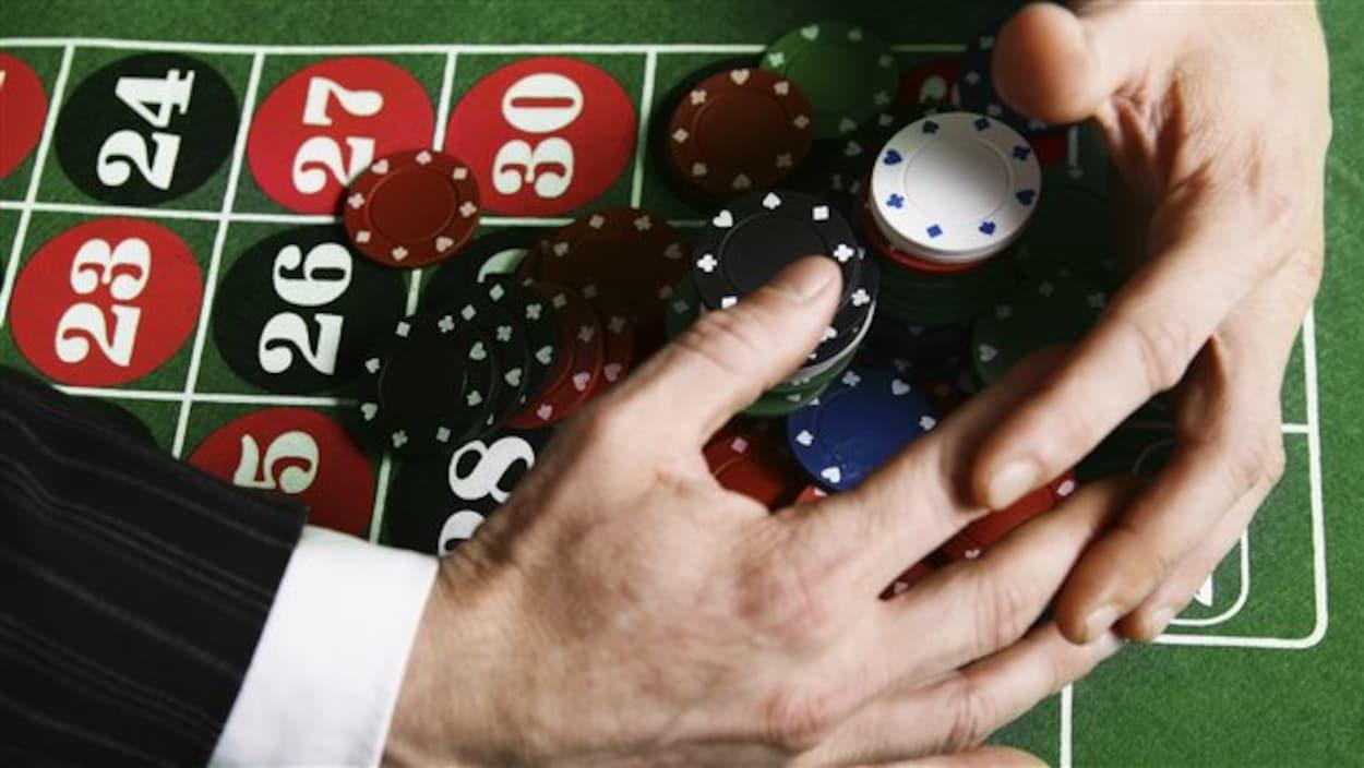 Un tapis de jeu de casino avec des jetons, des mains en train de se saisir de tous les jetons.