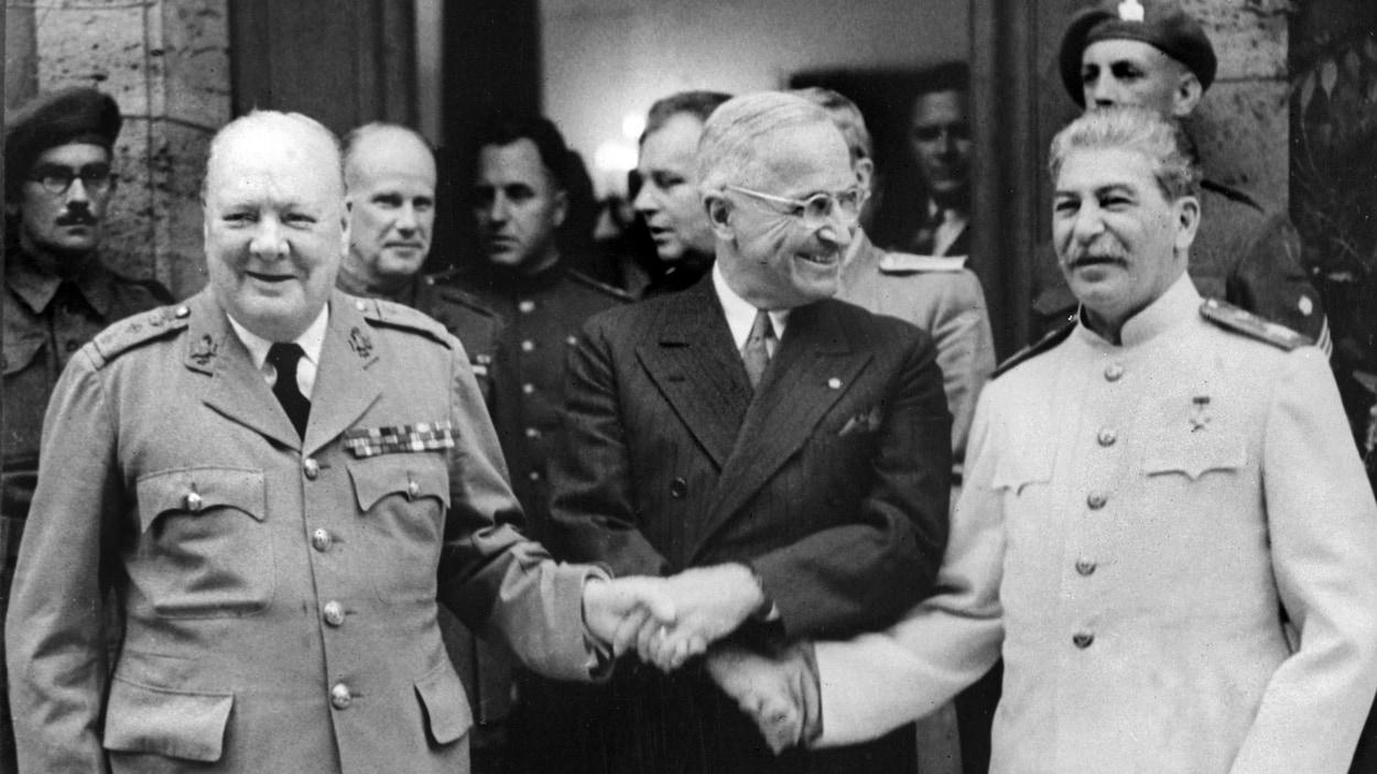 Photo d'archives sur les marches d'un édifice. Les trois dirigeants sourient et se serrent la mai.