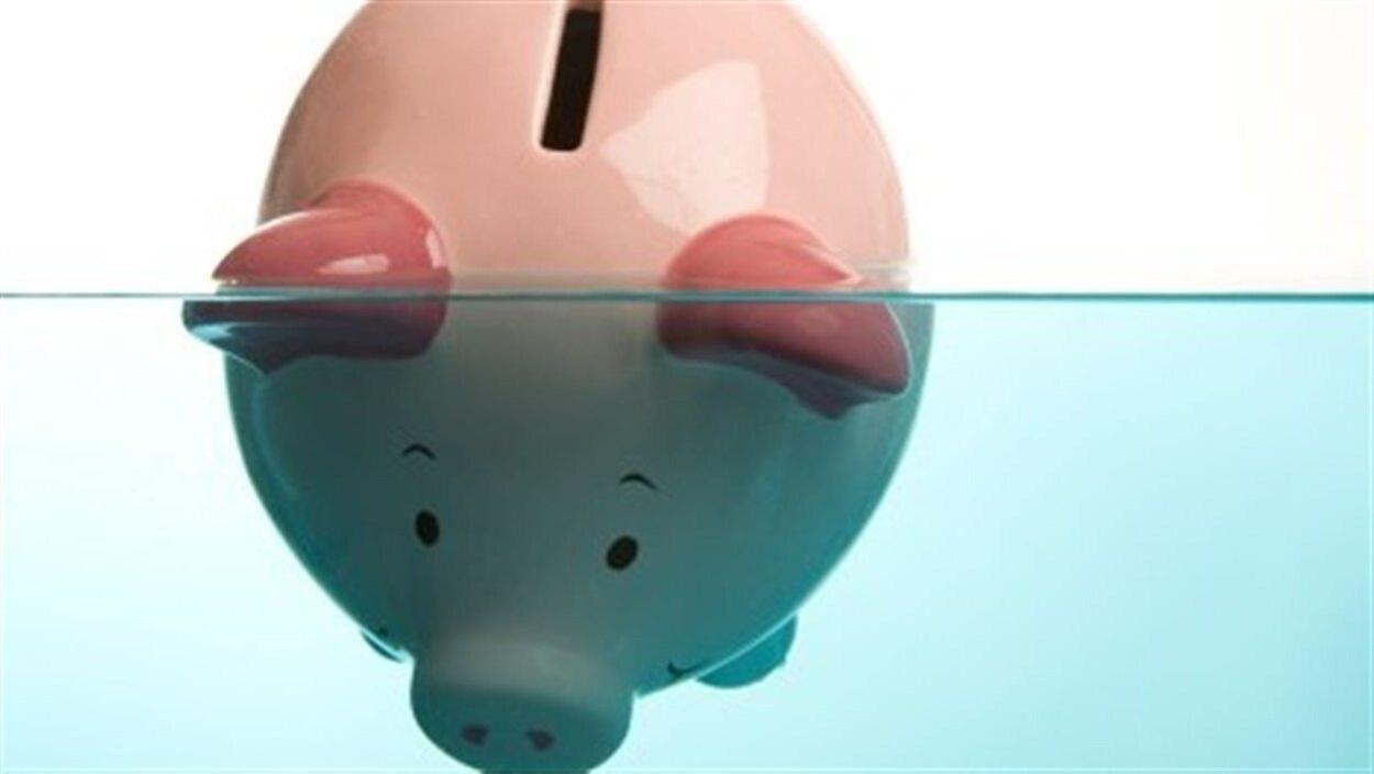 Une tirelire en forme de cochon est plongée dans l'eau.