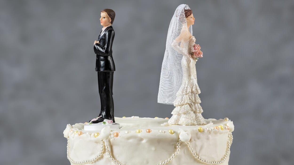Photo de deux figurines de mariés qui se tournent le dos sur le dessus d'un gâteau de mariage.