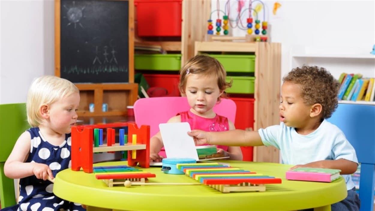 Trois enfants à une table avec des jouets.