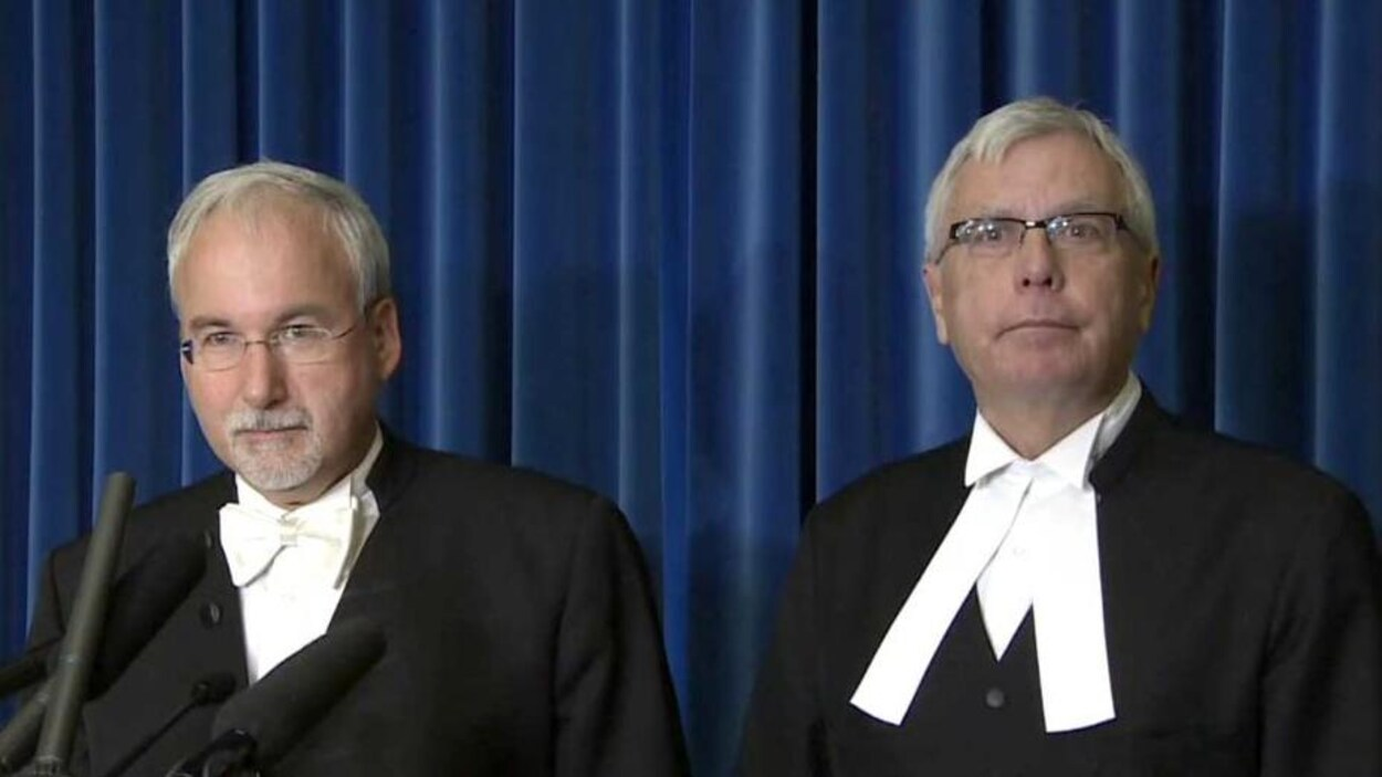 Deux hommes aux cheveux blancs assis côte à côte.