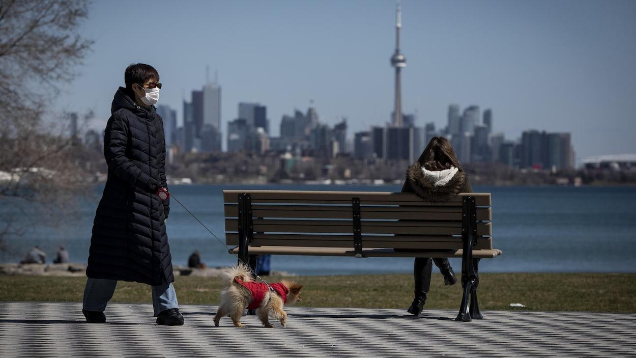 Une femme avec un masque passe à distance d'un banc public sur lequel une autre femme est assise. Cette dernière regarde la ville de Toronto.