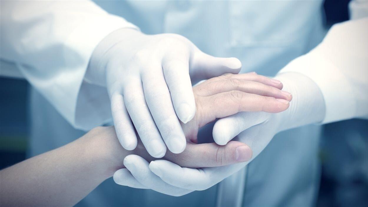 Des mains gantées tiennent la main d'un patient.