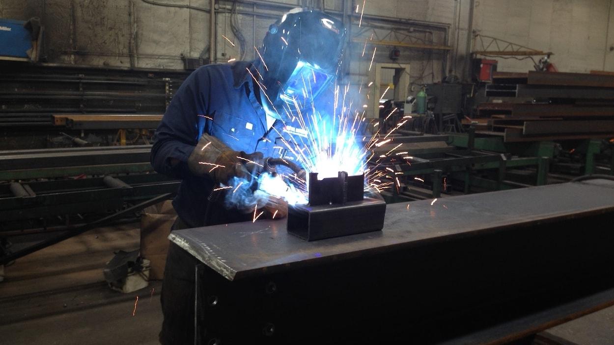 Un soudeur travaille sur une poutre d'acier.
