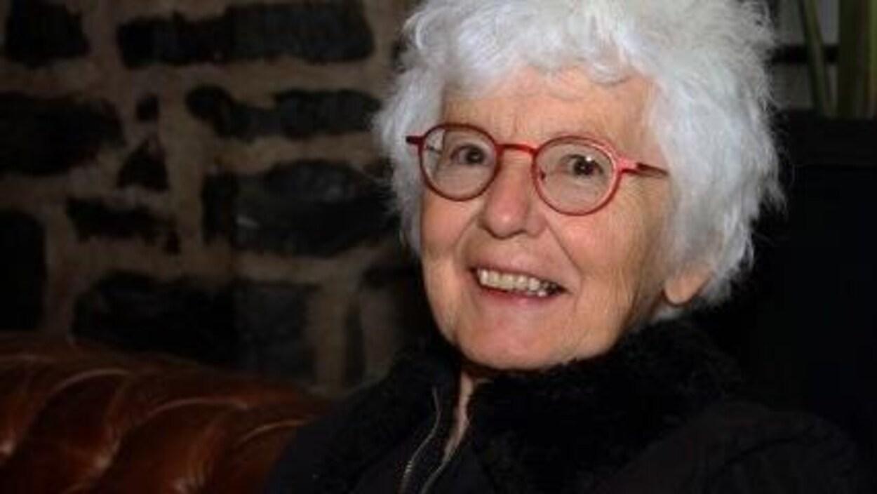 Une femme âgée souriant.
