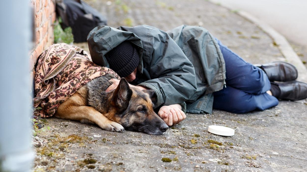 Un jeune itinérant dort appuyé sur son chien.