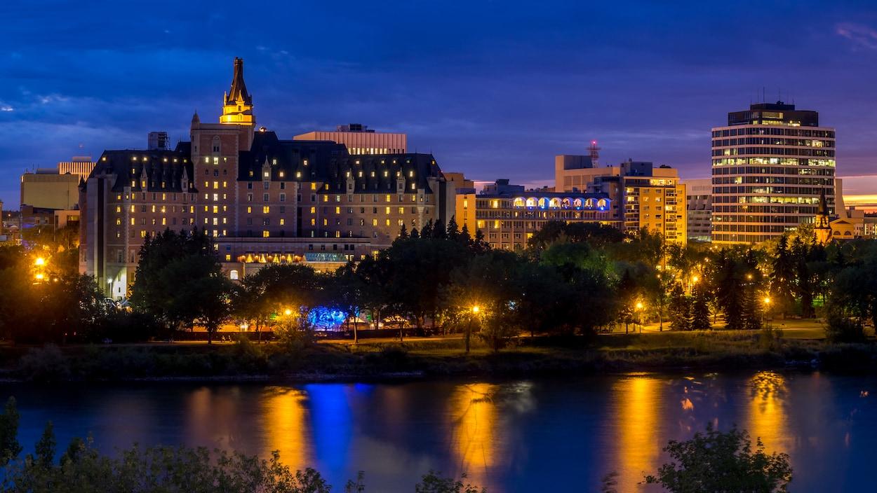 Le centre ville de Saskatoon de nuit, illuminé, avec la rivière passant devant.