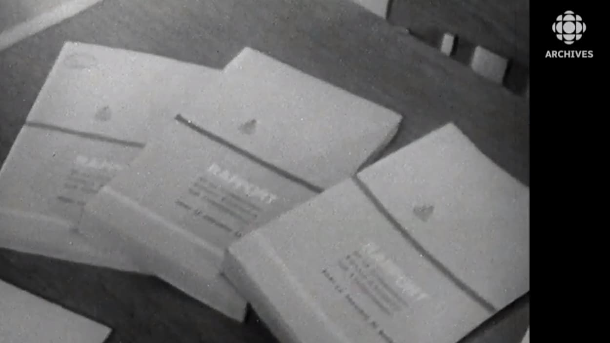 Sur une table se trouvent les premiers volumes publiés de la commission Parent.