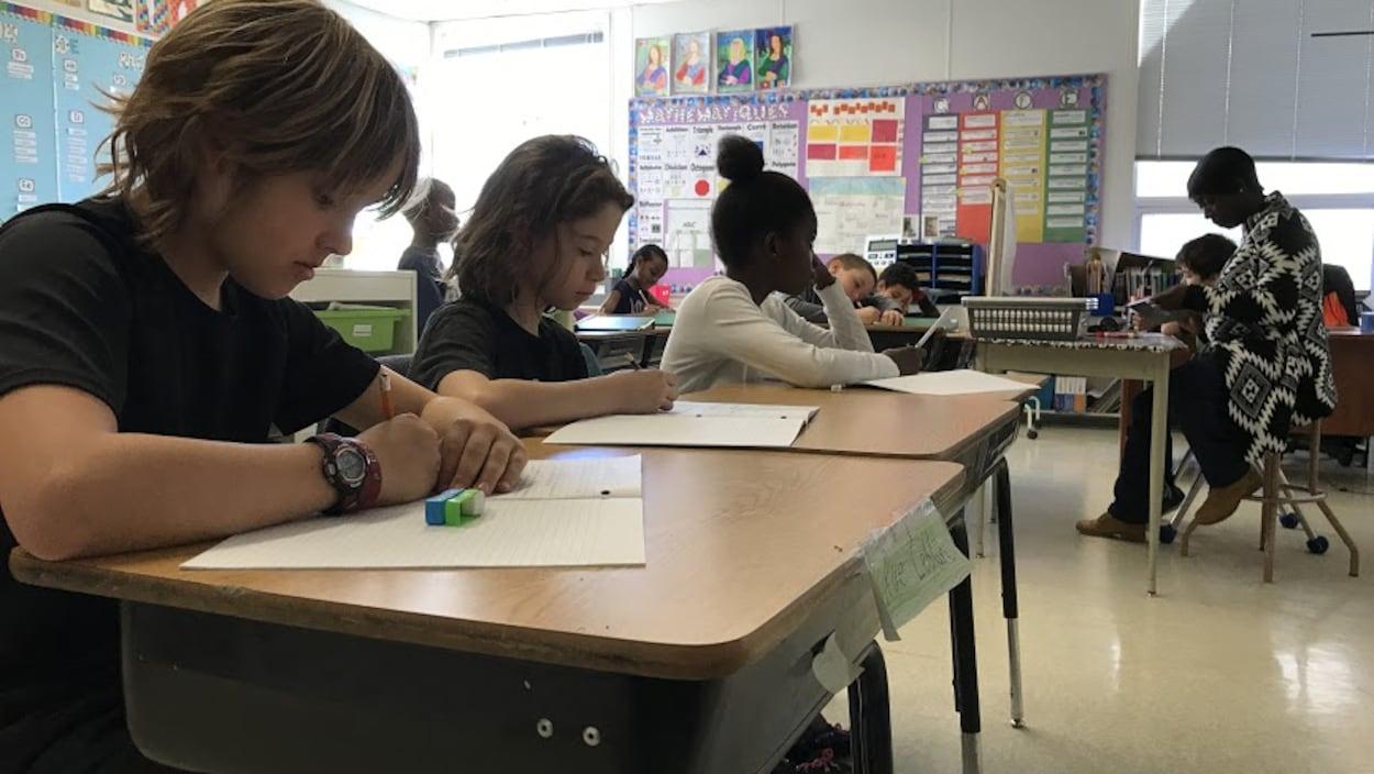 Une enseignante de l'École Précieux-Sang supervise des élèves  dans sa classe de 5e année.