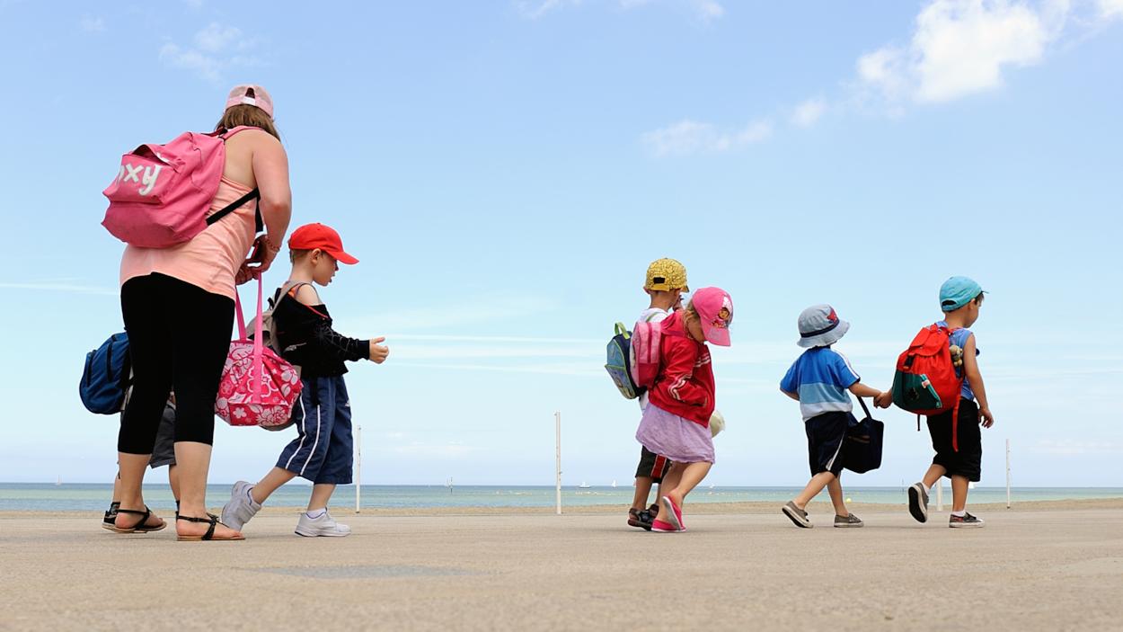 Une femme et des enfants se baladent près de l'océan.