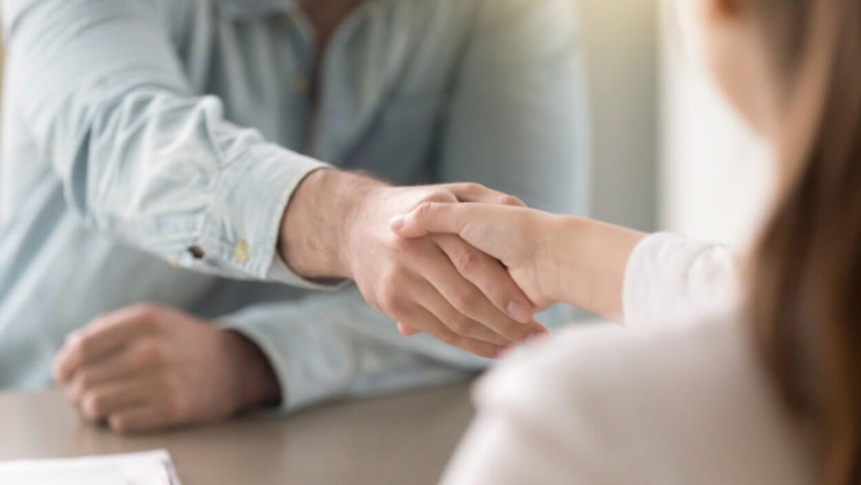 Un homme et une femme se serrent la main.
