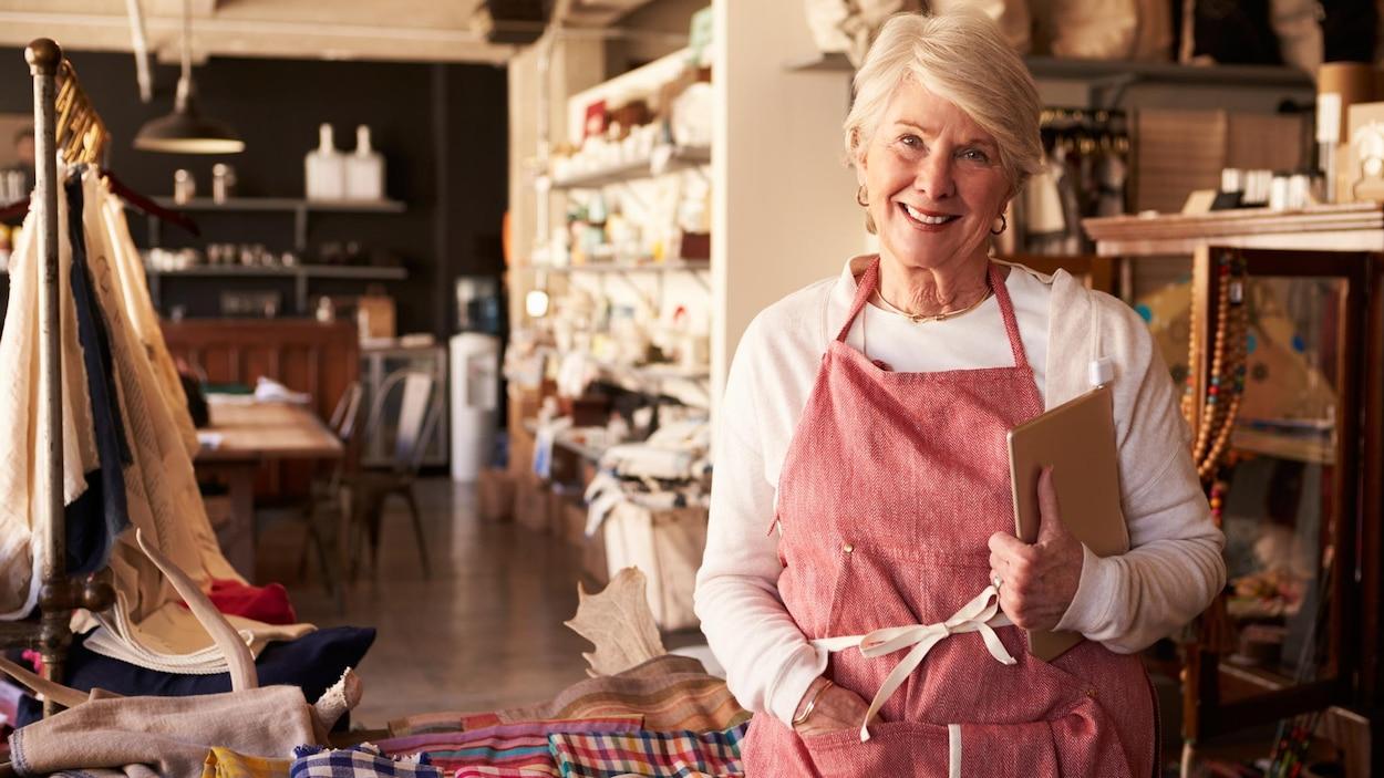 Une femme âgée travaille dans un commerce.