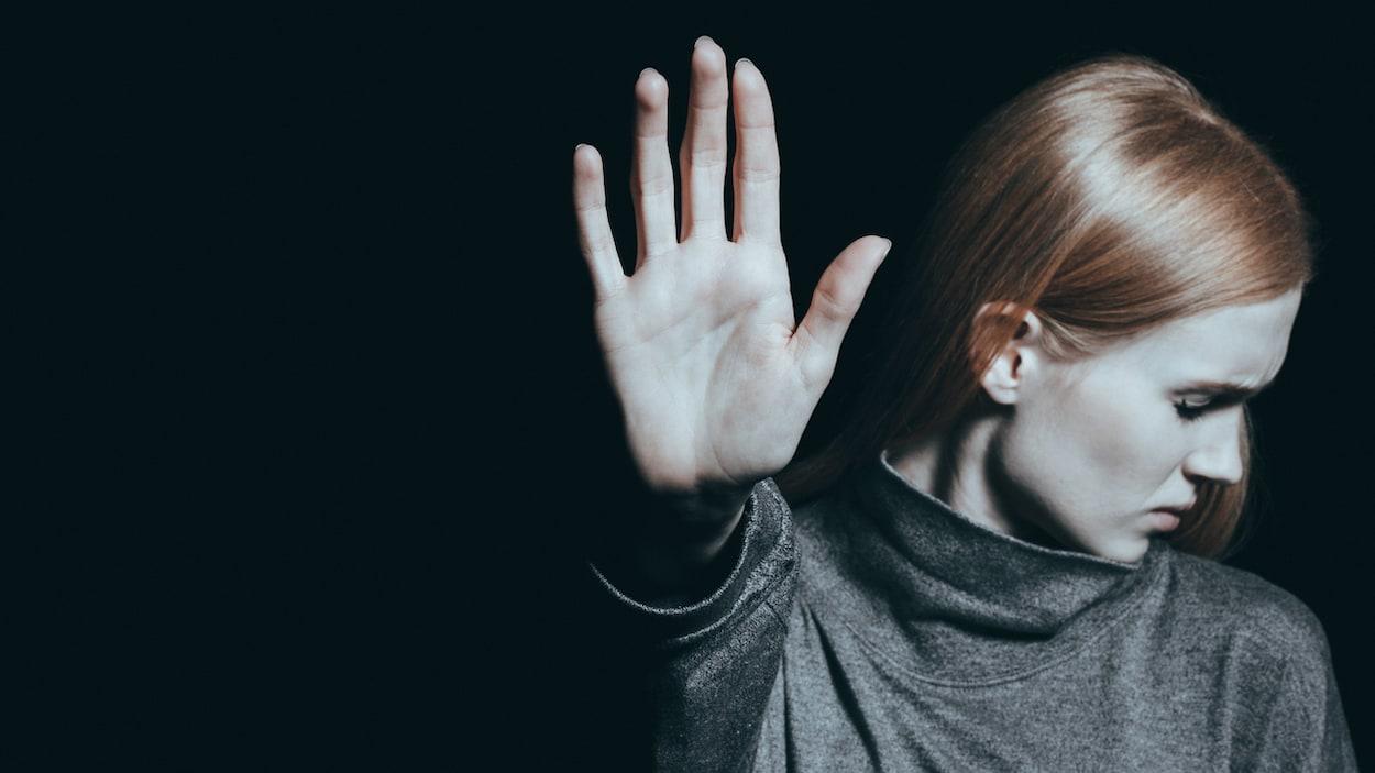 Une jeune femme met sa main devant elle pour signifier son refus