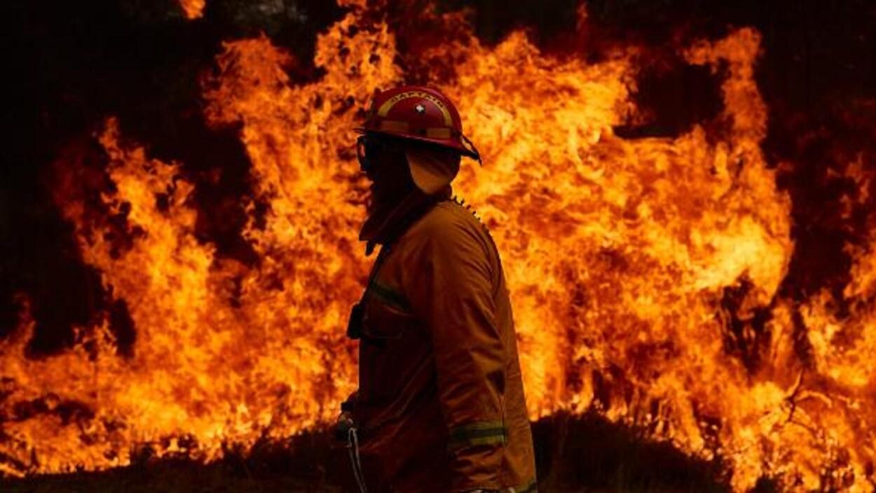 Un pompier à l'avant-plan avec un énorme brasier forestier en arrière-plan, à Sydney, en Australie.