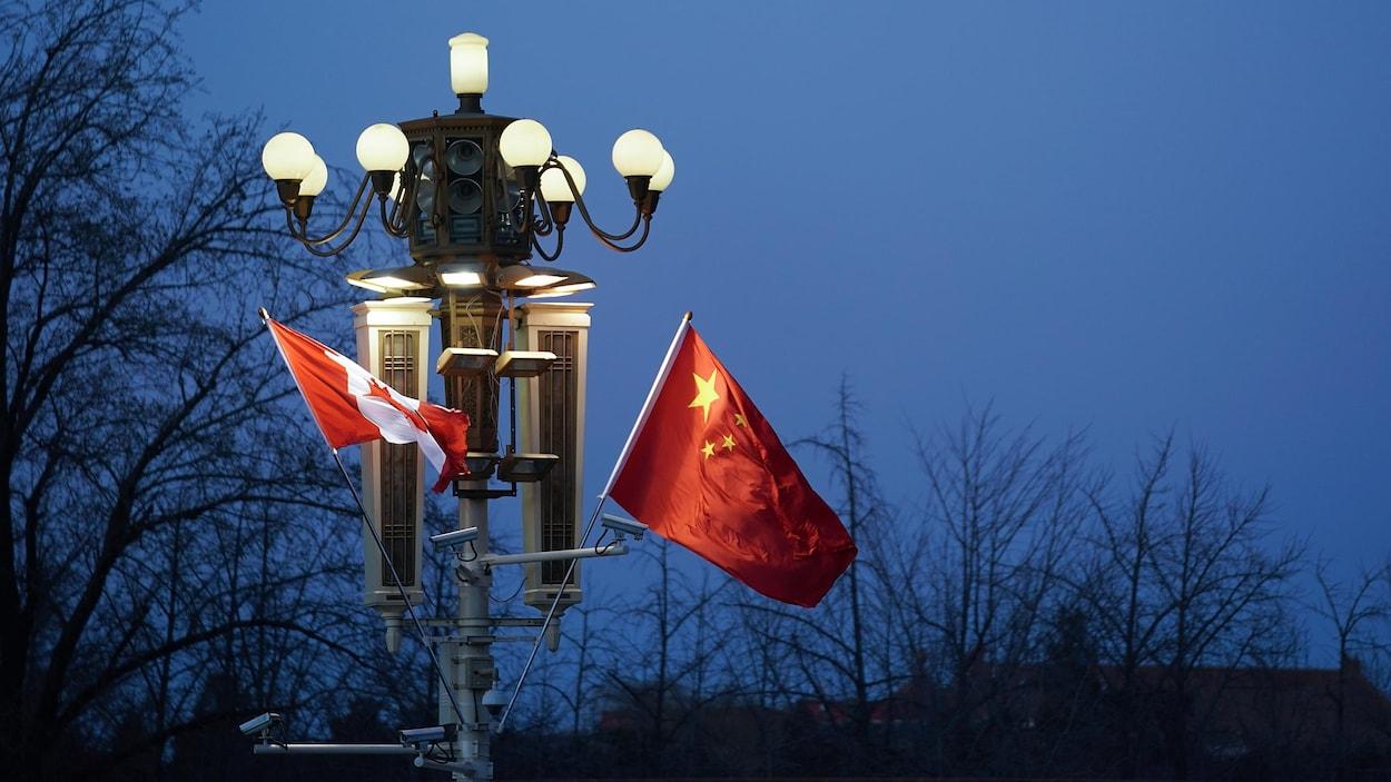 Le soir, un drapeau du Canada et un drapeau de la Chine flottent côte à côte sur un lampadaire allumé.