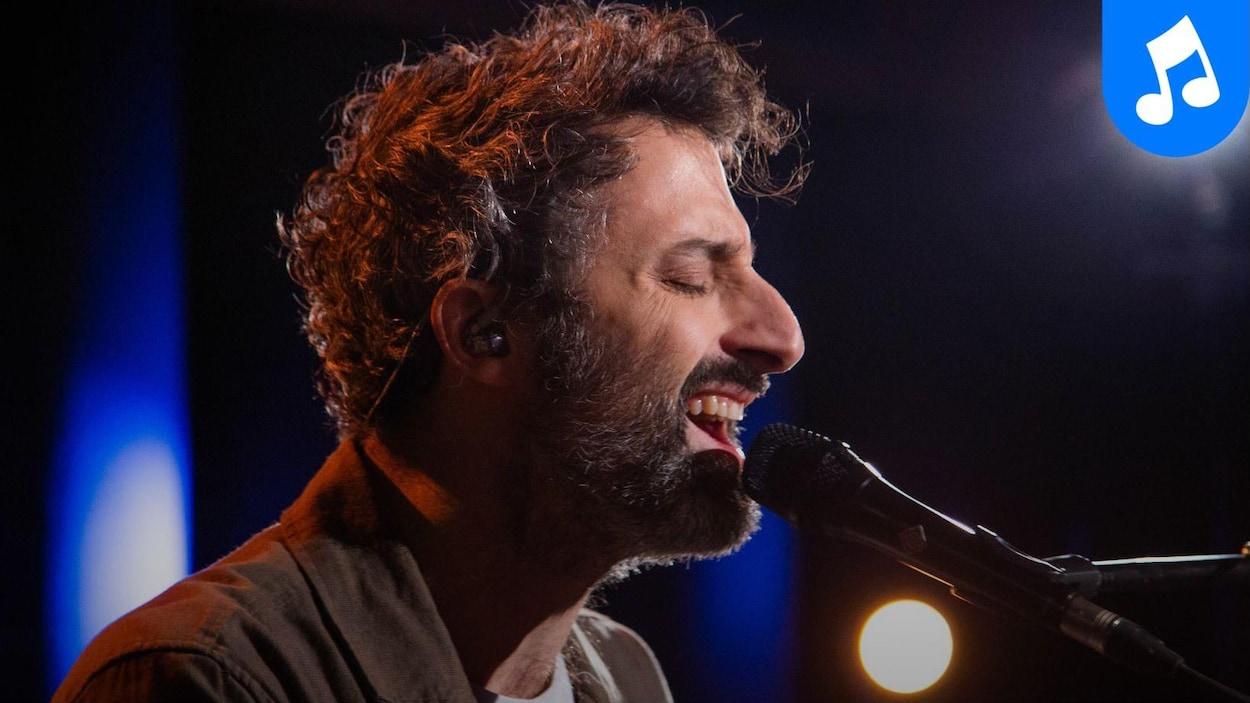 Le musicien Louis-Jean Cormier, de profil, chante dans un microphone.