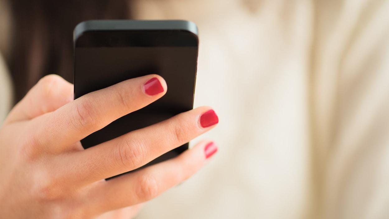 Une main de femme tient un téléphone cellulaire.