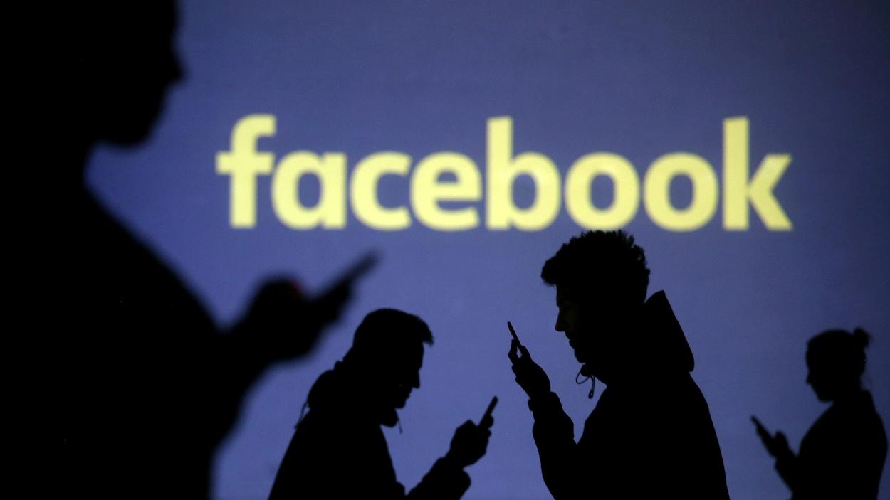 Des silhouettes d'utilisateurs de téléphones intelligents devant le logo de Facebook.