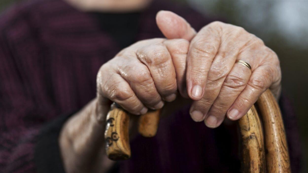 Les mains d'une personne âgée tenant une canne.