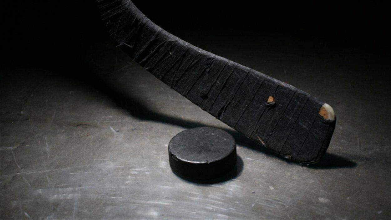 Un bâton de hockey et une rondelle reposent sur une surface glacée.