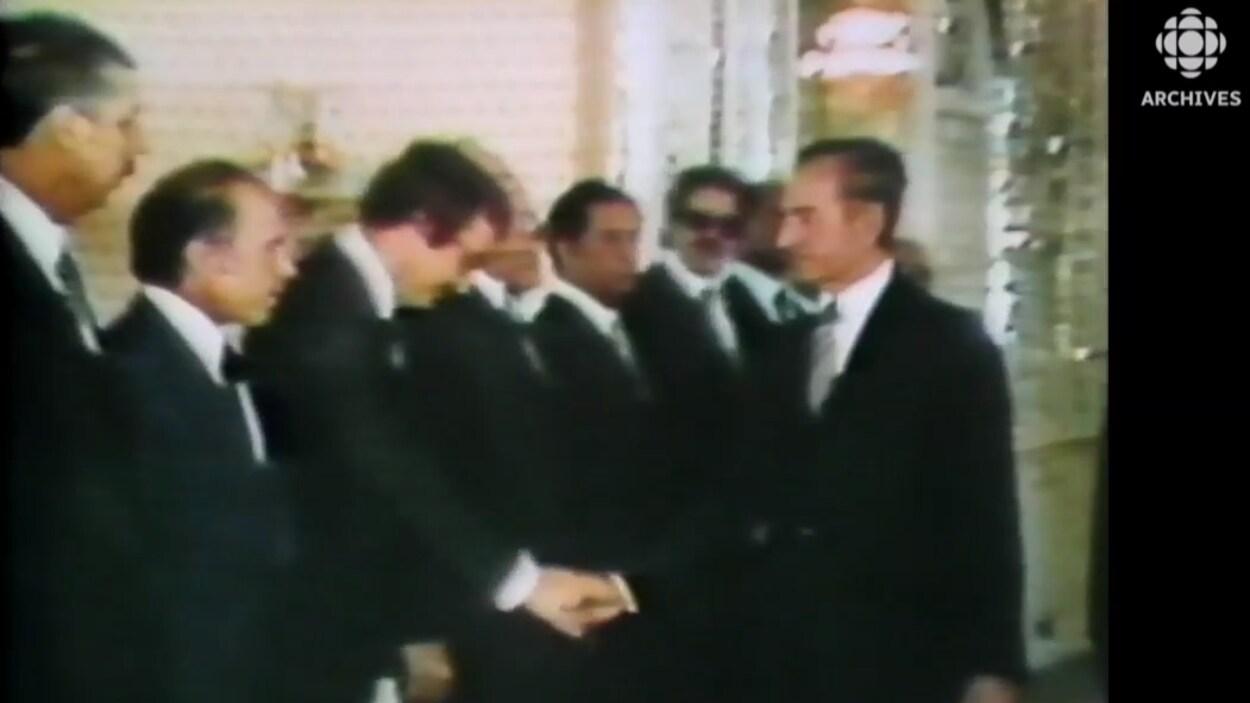 Le shah donne la main aux nouveaux membres du cabinet qu'il vient de nommer juste avant son départ pour l'Égypte.
