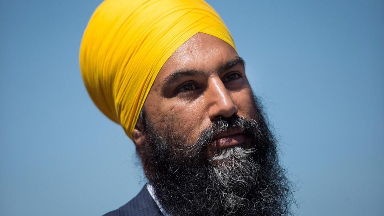 Un homme avec un turban jaune est photographié plan épaule sur fond bleu.