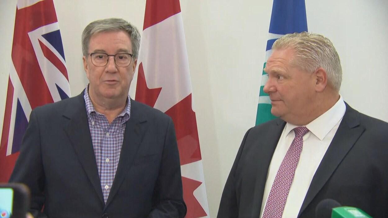 Jim Watson et Doug Ford s'adressent aux médias devant les drapeaux de l'Ontario, du Canada et de la Ville d'Ottawa.