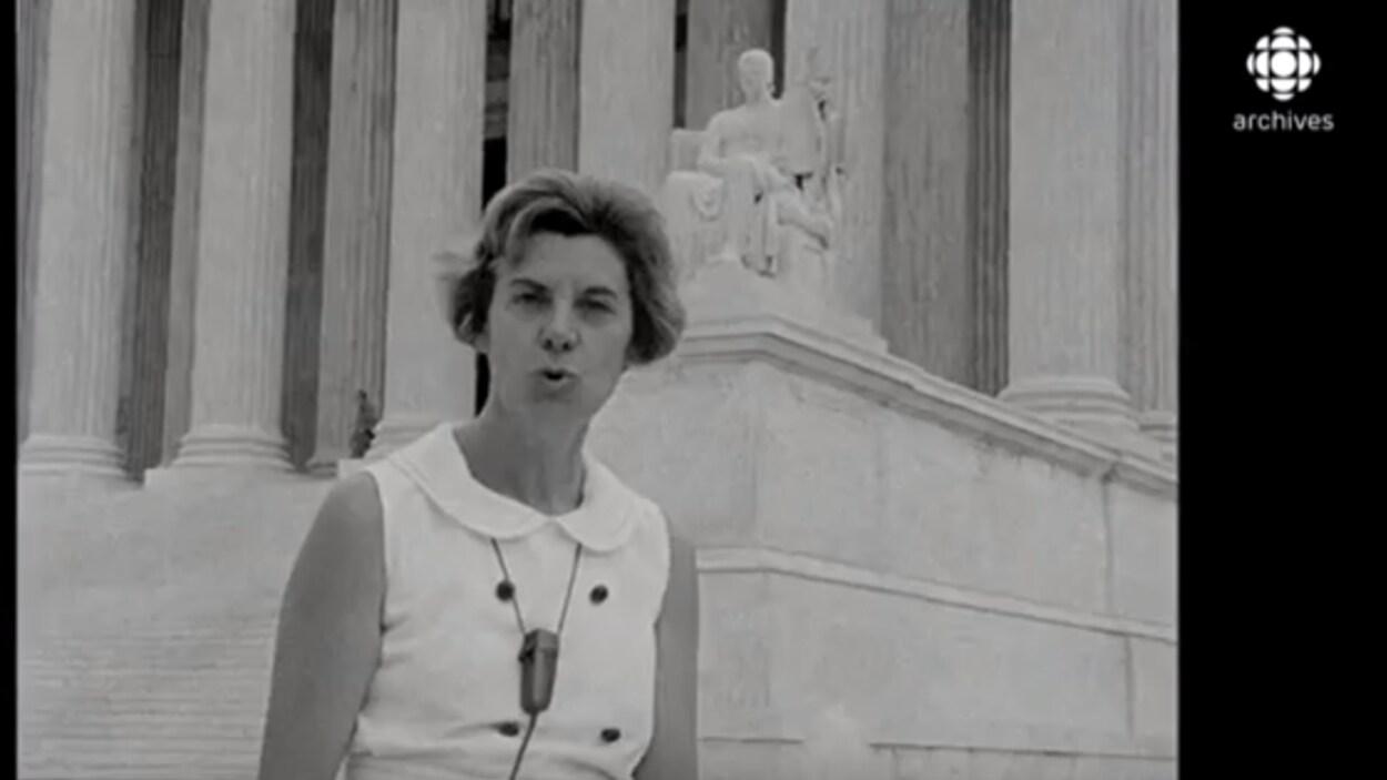 Judith Jasmin vêtue de blanc se tient debout devant la colonnade de la Cour suprême des États-Unis à Washington.