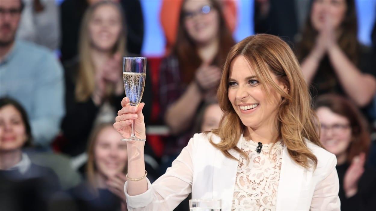 L'animatrice Julie Snyder, avec un veston blanc, un verre de champagne à la main.