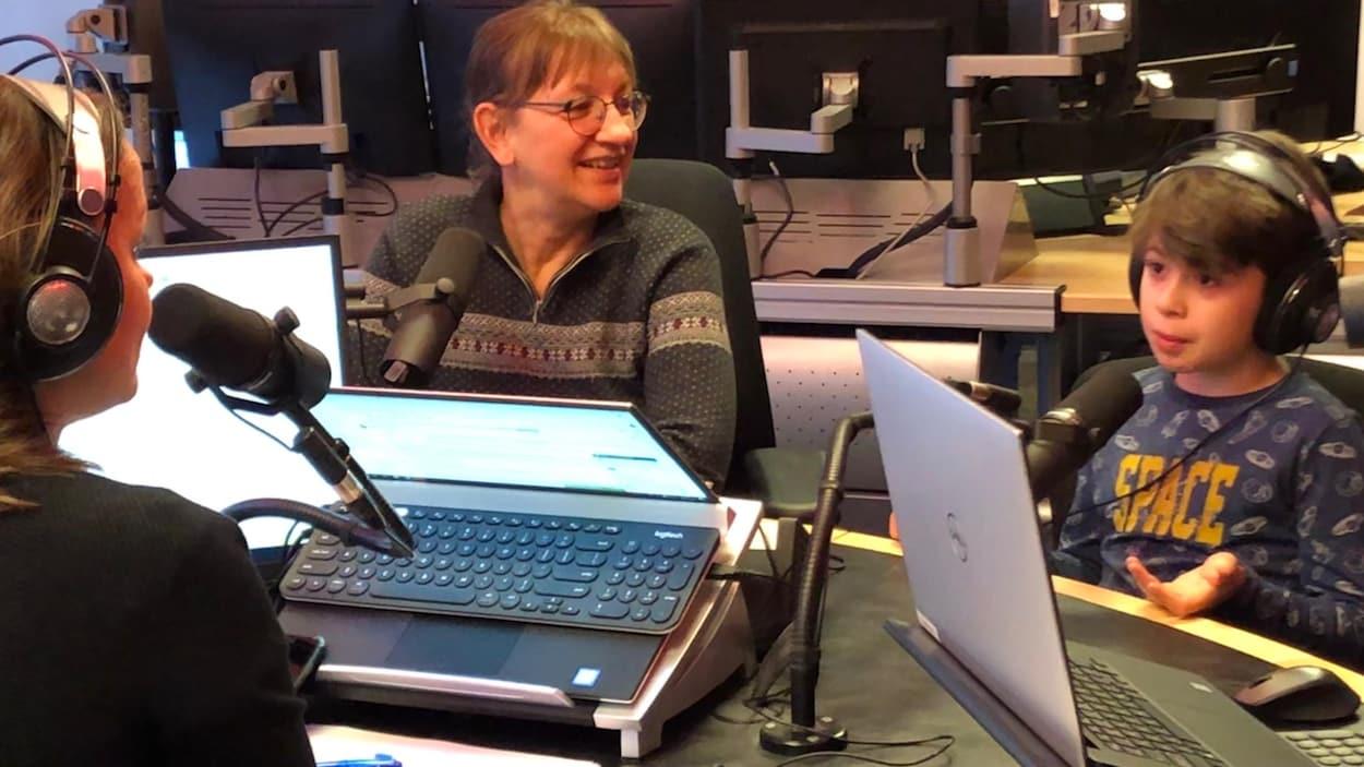 Trois personnes discutent dans un studio de radio.