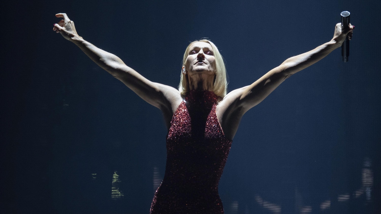 Céline Dion, bras levés et yeux fermés, sur scène.