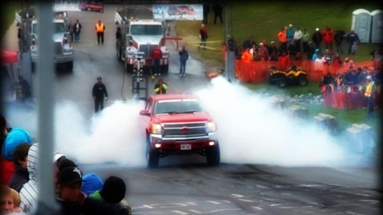 Une camionnette tire un grand camion lors d'une course au Smooth Truck Fest
