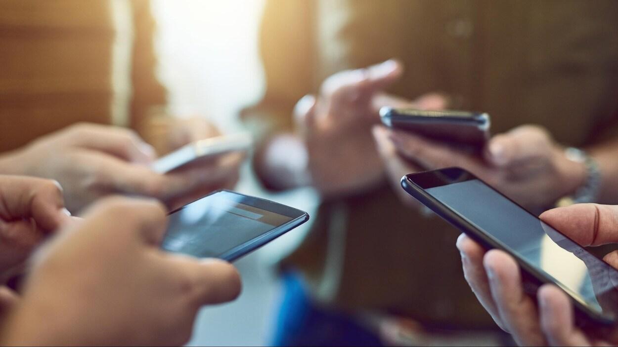 Des jeunes consultent leur téléphone cellulaire.