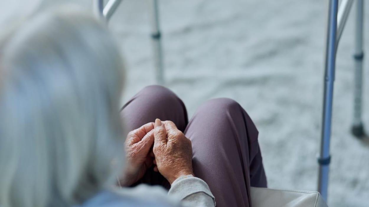 Une femme âgée assise à côté de son déambulateur.