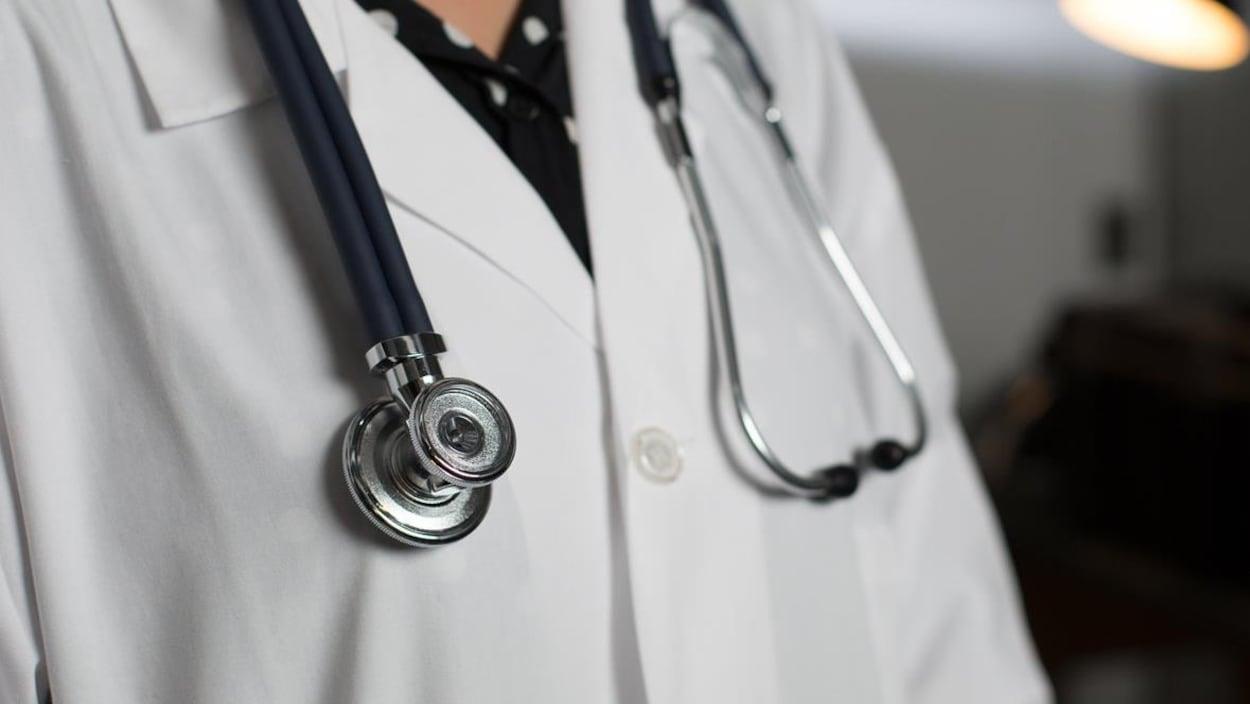 Haut de corps d'un médecin portant un stéthoscope autour de son cou.