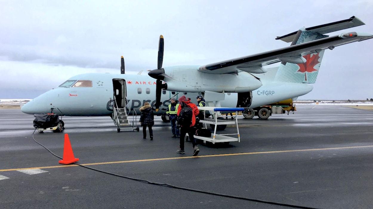 Des passagers embarquent dans un avion à l'aéroport des Îles-de-la-Madeleine.