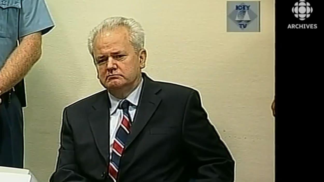 Slobodan Milosevic est assis lors de sa première comparution au Tribunal pénal international pour l'ex-Yougoslavie.