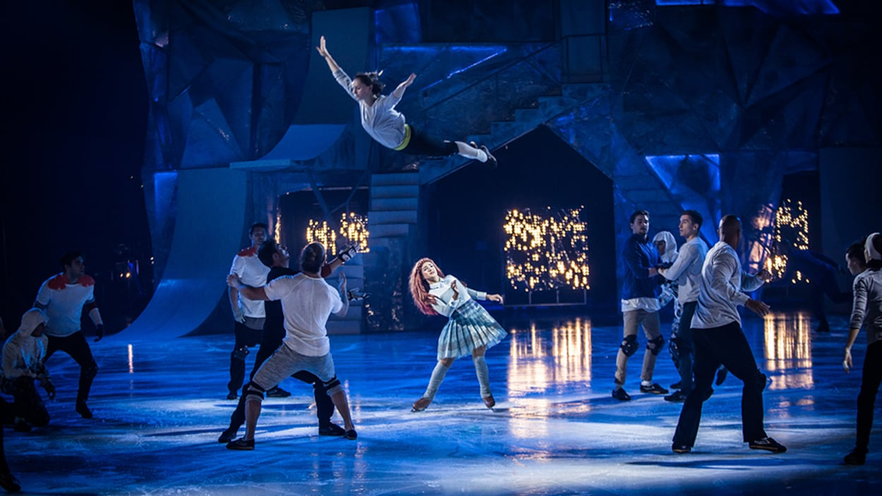 Une patineuse voltige dans les airs tandis que d'autres patineurs l'observent dans cette scène de <i>Crystal</i>, le nouveau spectacle du Cirque du Soleil.