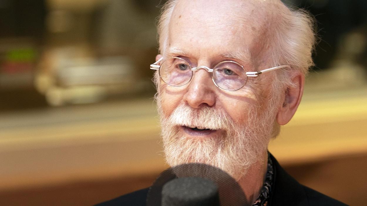 Un vieil homme parle devant un micro.