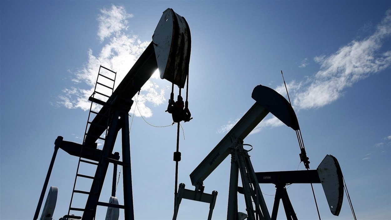 Trois pompes de pétrole devant un ciel bleu