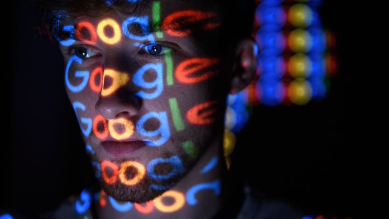 Le logo de Google luit sur le visage d'un homme dans la pénombre.