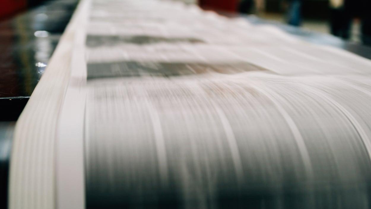 Des journaux en cours d'impression dans une presse rotative