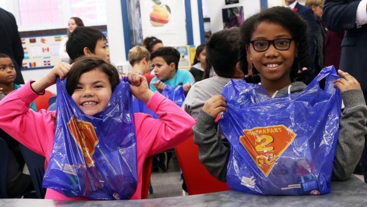 Des enfants montrent fièrement leur sac bleu avec la mention Breakfast2Go.