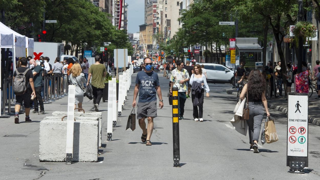 Des gens marchent sur la rue Sainte-Catherine, qui est piétonne.