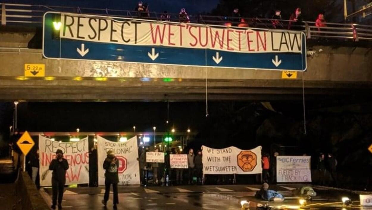 Des hommes et femmes dans la nuit qui protestent avec des banderoles.
