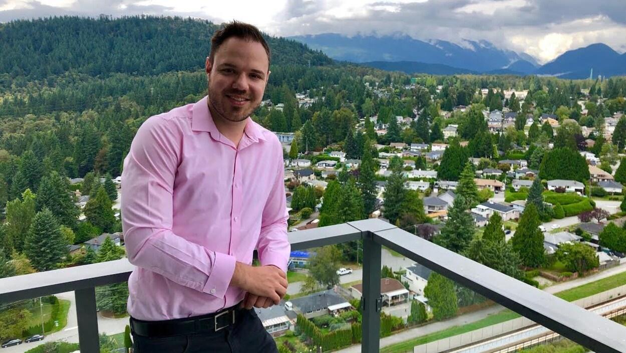 Un homme est accoté sur le garde-fou de sa terrasse, avec une vue sur la ville.