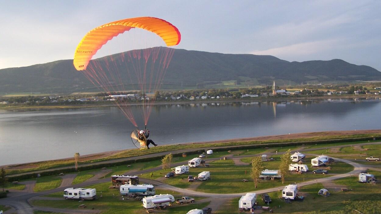 On voit un adepte de paramoteur qui vole au-dessus du camping de Carleton-sur-Mer