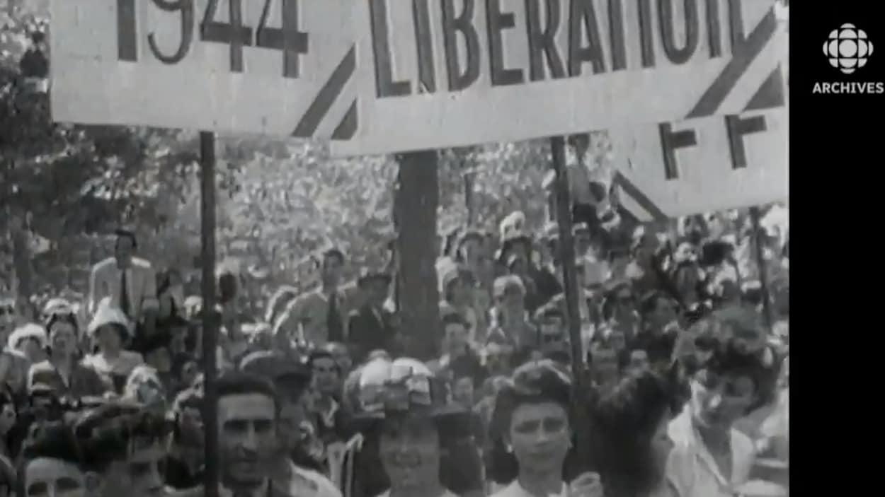 Des Parisiens brandissent des pancartes célébrant la libération de Paris le 25 août 1944.