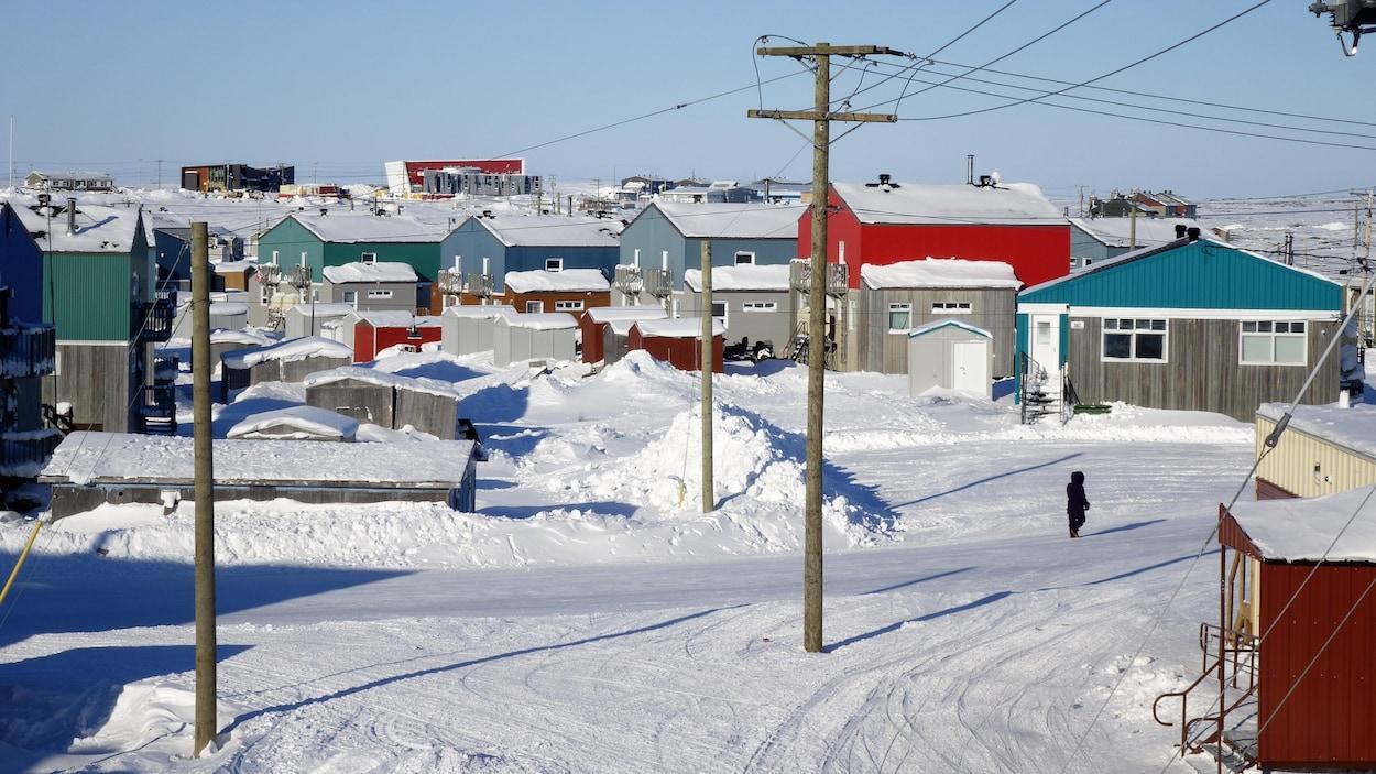 Vue d'un village enneigé, composé de dizaines de maisons colorées.